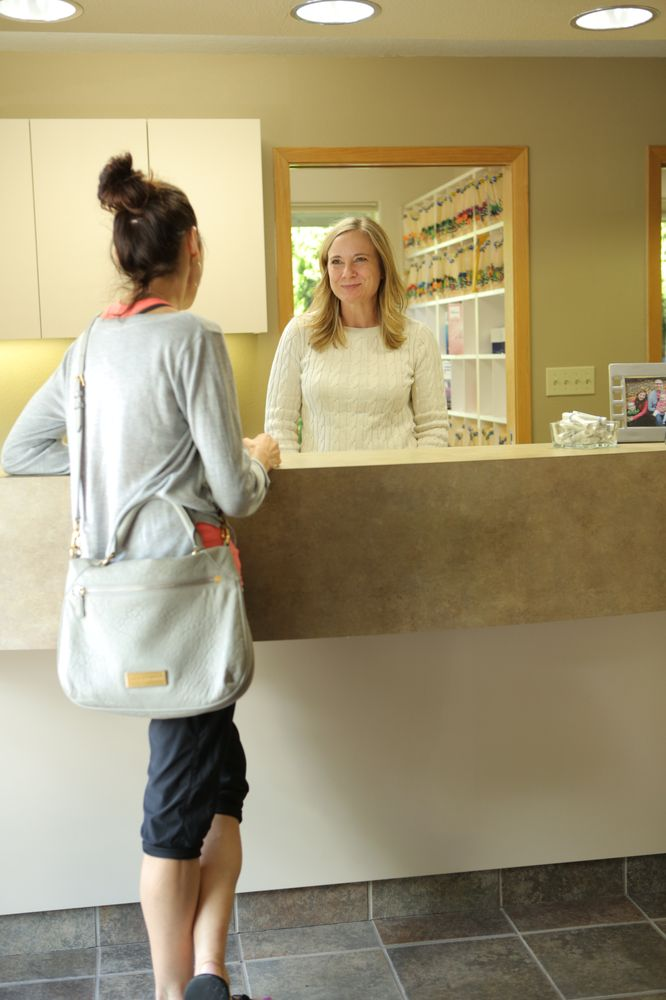 A patient at reception talking to the receptionist at Roane Family Dental.